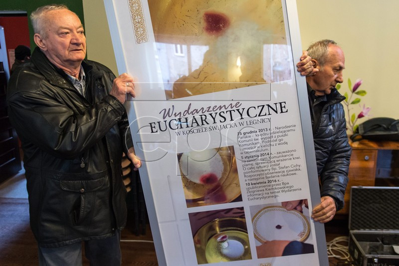 epa05255722 Banner with information about miracle before a press conference at the St. Jack Church in Legnica, Poland, 12 April 2016. On 11 April 2016 the Bishop of Legnica Zbigniew Kiernikowski announced the signs of the Eucharistic miracle that happened at the St. Jack Parish in Legnica during the Holy Communion on 25 December 2013 whena consecrated Host fell to the floor, was picked up and placed in a water-filled container (vasculum). Soon after, stains of red colour appeared and former Legnica bishop Cichy set up a commission to observe the phenomenon. In February 2014, a tiny red fragment of the Host was seperated and put on a corporal. The Commission ordered to take samples in order to conduct a thorough tests by the relevant research institutes. the Department of Forensic Medicine in Szczecin conducted research and announced that in the histopathological image, the fragments of tissue have been found containing the fragmented parts of the cross striated muscle, which is most similar to the heart muscle with alterations that often appear during the agony. The genetic researches indicate the human origin of the tissue. The Congregation for the Doctrine of the Faith in the Vatican advised to expose the host for faithful. The host in a special monstrance will be exposed to public in early June in the St. Jack Parish in Legnica. EPA/MACIEJ KULCZYNSKI POLAND OUT