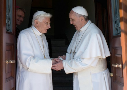 Retired Pope Benedict XVI greets Pope Francis at Vatican