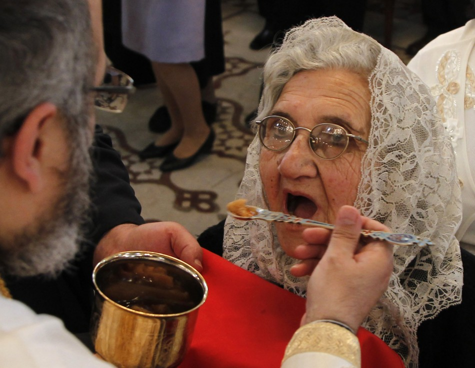woman-takes-communion-clergyman-during-mass-orthodox-easter-roman-orthodox-patriarchate